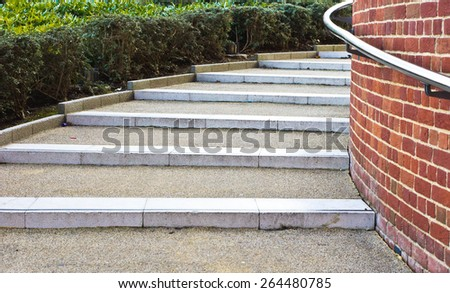 Modern stone steps in a UK town with a metal railing - stock photo