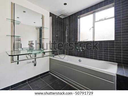 modern stone tiled bathroom with luxury glass hand wash basin - stock photo