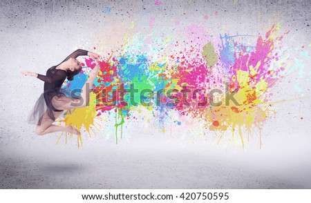 Modern street dancer jumping with colorful paint splashes on back wall concept - stock photo