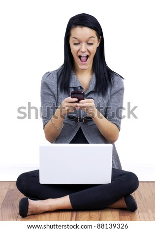 Modern student life: Young woman happy or surprised while reading and texting on her cell phone with white laptop computer on her crossed legs. - stock photo