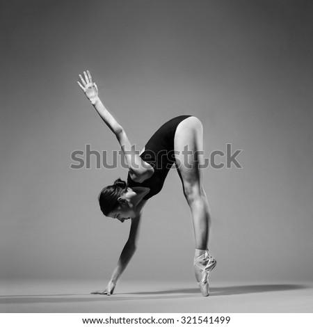 Modern style ballet dancer posing on studio background. Extreme flexibility, grayscale image. - stock photo