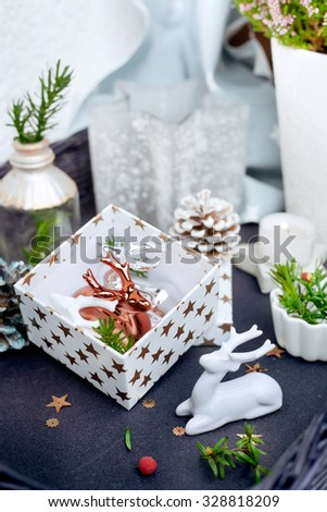 Modern style Christmas decor - ceramic reindeer in copper, silver and white colors, gift box and candles on coffee table. Natural light. Toned photo. Focus on the white and copper reindeer. - stock photo