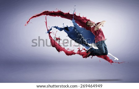 Modern style dancer in jump and color paint splashes at background - stock photo