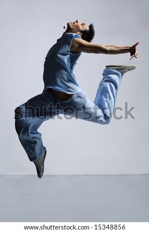 modern style dancer jumping on grey background - stock photo