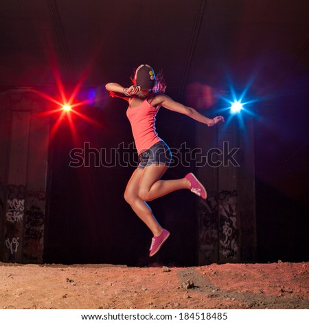 Modern style dancer jumping outdoors