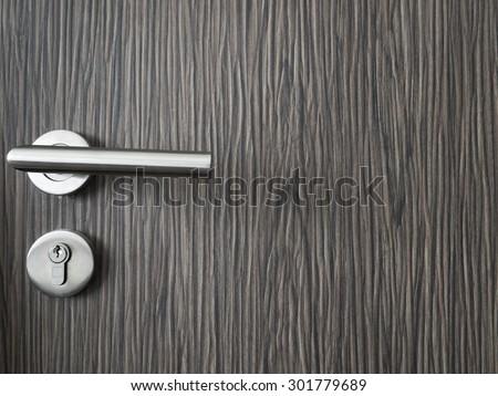 Modern style door handle on natural wooden door, selective focus - stock photo