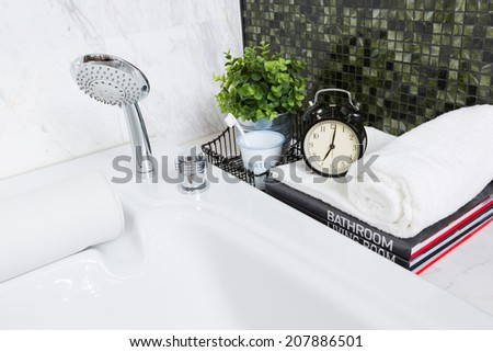 Modern style luxurious jacuzzi bathtub with alarm clock in early morning - stock photo