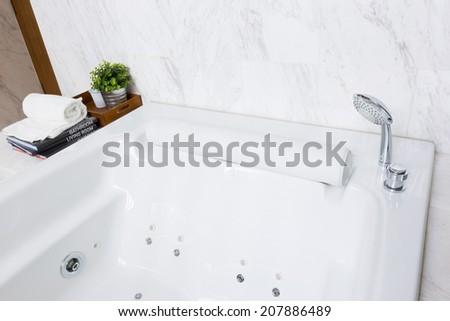 Modern style luxurious jacuzzi bathtub with white marble wall - stock photo