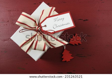 Modern style white and canvas stripe ribbon Christmas gift box on dark red recycled wood background with Merry Christmas gift tag. - stock photo