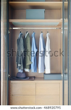 Modern style wooden closet with shirts hanging on rail