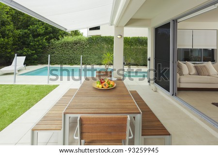 Modern suburban backyard and living room with table setting and swimming pool