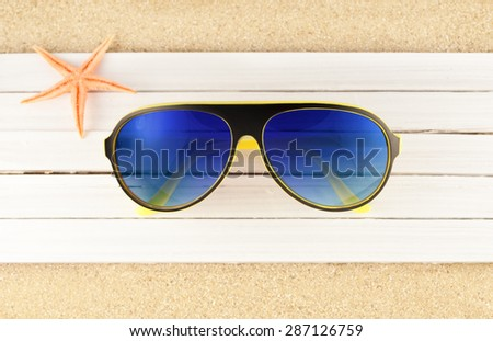 Modern sunglasses on a wooden planks over sandy background. - stock photo