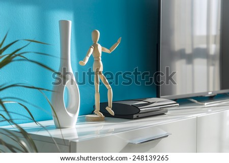 Modern sunny living room with vase and wooden figure - stock photo