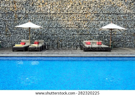 Modern Swimming Pool with stone wall - stock photo
