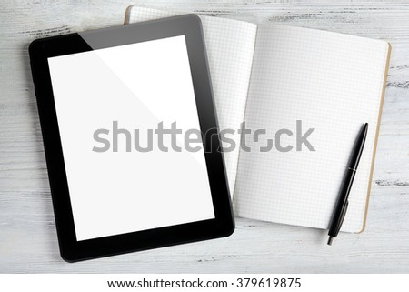 Modern tablet and notebook on white wooden background - stock photo