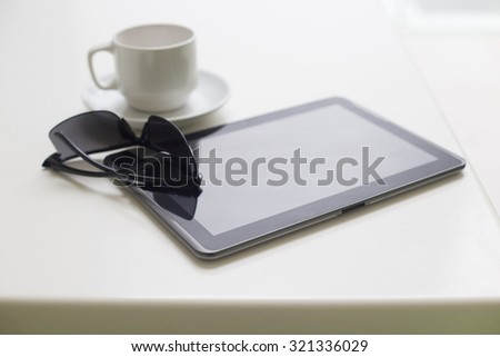 Modern tablet with coffee cup on white background