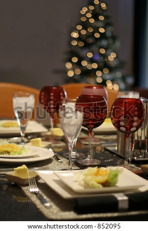 Modern tableware with christmas tree in the background - stock photo