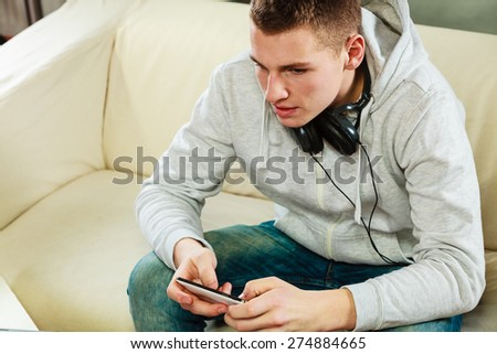Modern technologies connection leisure concept. Young handsome man relaxing on couch with headphones smartphone at home