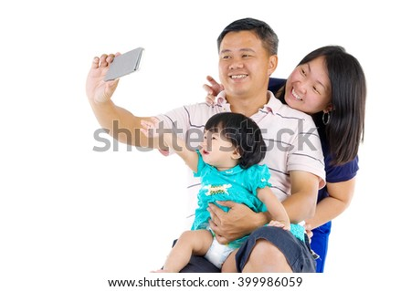 Modern technology, age and people concept. Asian baby girl with his parent taking selfie, using smartphone, self photographing. - stock photo