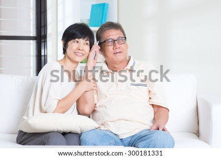 Modern technology, age and people concept. Mature Asian couple using smart phone. Family living lifestyle at home. - stock photo