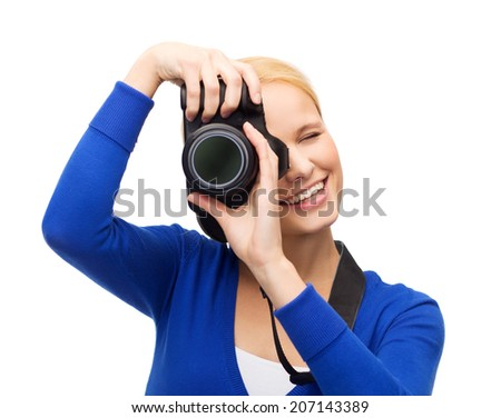 modern technology and people concept - smiling woman in casual clothes taking picture with digital camera - stock photo