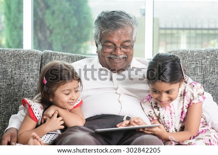 Modern technology concept. Grandparent and grandchildren using touch screen tablet computer. Portrait Indian family at home. Asian people living lifestyle. - stock photo