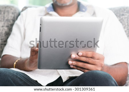 Modern technology. Mature Indian man using touch screen digital tablet computer at home. Asian people living lifestyle indoors. - stock photo