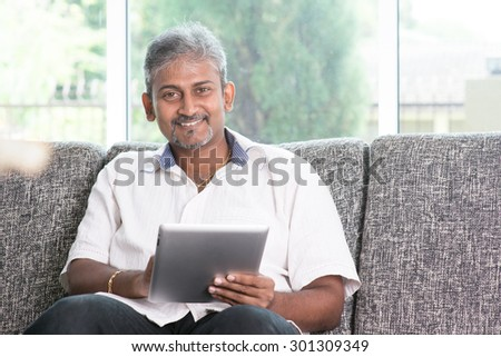 Modern technology. Mature Indian man using touch screen tablet computer at home. Asian people living lifestyle indoors. - stock photo