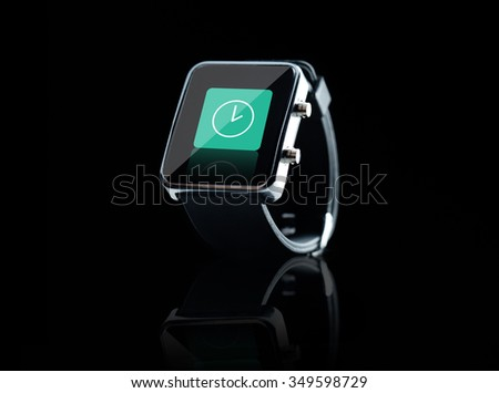 modern technology, time, object and media concept - close up of black smart watch with clock icon on screen over black background - stock photo