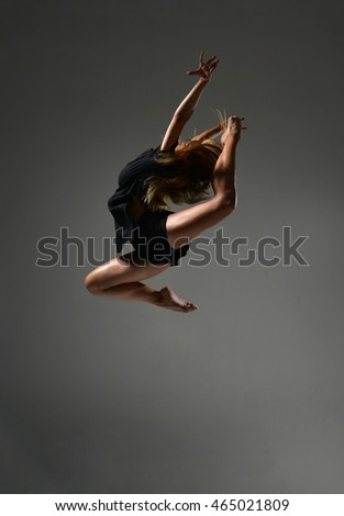 Modern teenage girl dancer jumping and dancing hip-hop in black tshirt on dark background