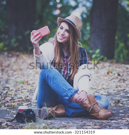 Modern teenage girl in autumn in park sitting taking a selfie on smartphone. Trendy young woman in jeans, boots, sweater and plaid shirt with camera and coffee next to her. Square format, retouched. - stock photo