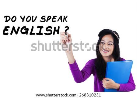 Modern teenage girl studying English and write Do You Speak English - stock photo