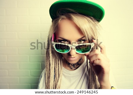 Modern teenage girl with blonde dreadlocks standing by the brick wall. Jeans style. Modern generation. - stock photo