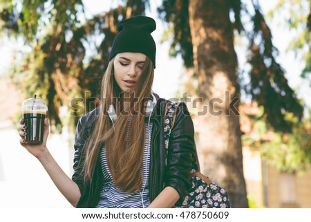 Modern teenage hipster girl in autumn in park in beanie hat, with takeaway coffee and headphones Millennial young woman in fall relaxing, drinking cappuccino. Matte filter, natural lighting.