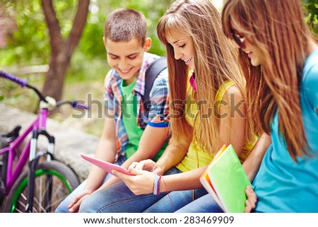 Modern teenagers browsing in touchpad outside