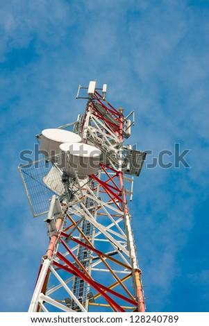 Modern telecommunication antenna, isolated on a blue sky - stock photo