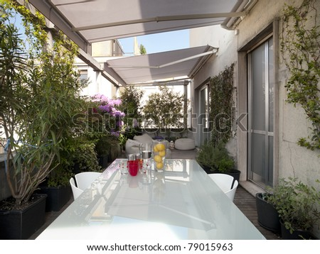 modern terrace with a glass table among plants and flowers - stock photo