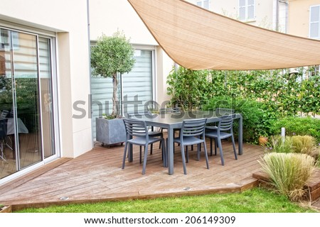 Modern terrace with dining table and chairs - stock photo