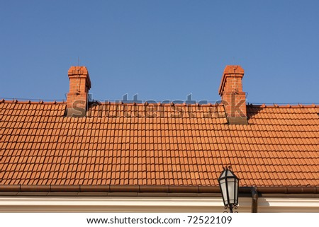 Modern tiles roof against the blue sky. - stock photo