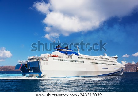 Modern tourist cruise ship sailing on Aegean sea, Santorini island, Greece. Sunny, blue sky.