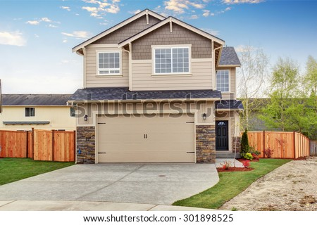 Modern town house with well kept lawn, and garage.