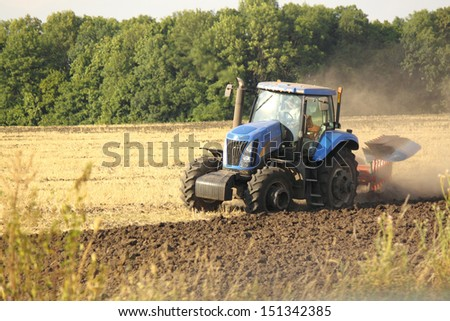 Modern tractor on the agricultural field - stock photo