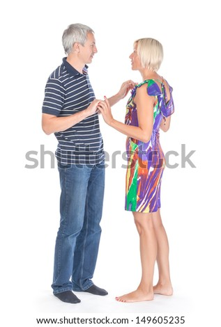 Modern trendy affectionate mature couple standing facing each other looking into each others eyes and holding hands, full length portrait on white - stock photo