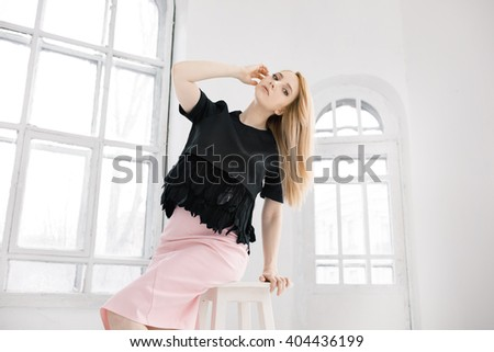 Modern trendy teenager girl. Studio shot against window. Copy space.