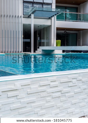 Modern tropical residence with swimming pool in summer - stock photo