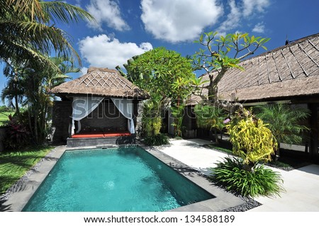 Modern tropical villa with swimming pool in nature - stock photo