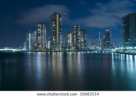 modern Tsukuda district of Tokyo at night over waters of Sumida River