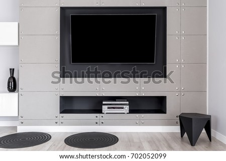 modern tv screen on wall with decorative metal panels