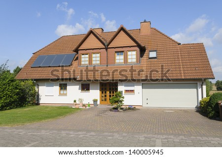 Modern two family house with solar cells and garage. - stock photo