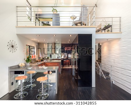 Modern two story loft with kitchen, bar chairs office area. - stock photo